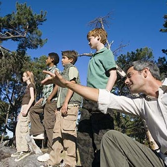 Teacher directing students in forest