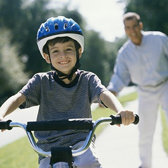 Boy cycling with his father standing behind him