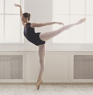 Beautiful ballerine stands in arabesque ballet position