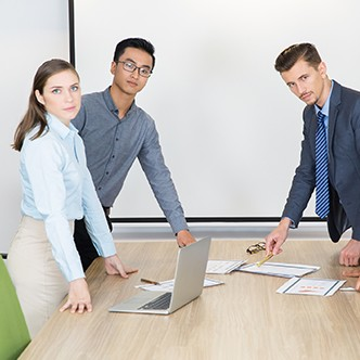 Serious young businesspeople standing in boardroom