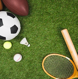 top view of various sport balls, baseball bat and glove, badminton racket on green lawn