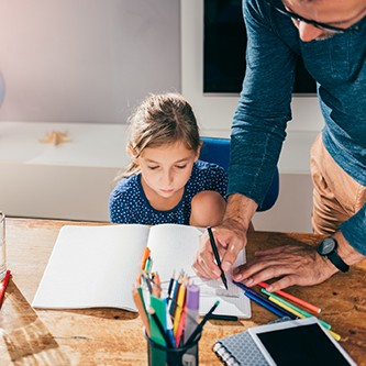 Father helping daughter to finish homework