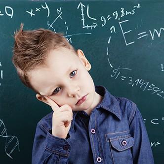 Little boy near blackboard with formulas