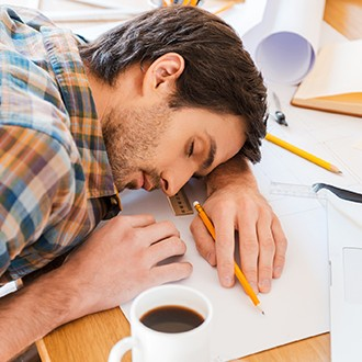 Man feeling exhausted and sleeping on working desk