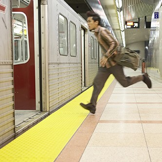 Young man running to subway train, side view