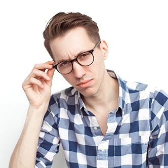 Thoughtful man touching glasses